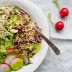 Runder Teller mit Salat auf Tuch