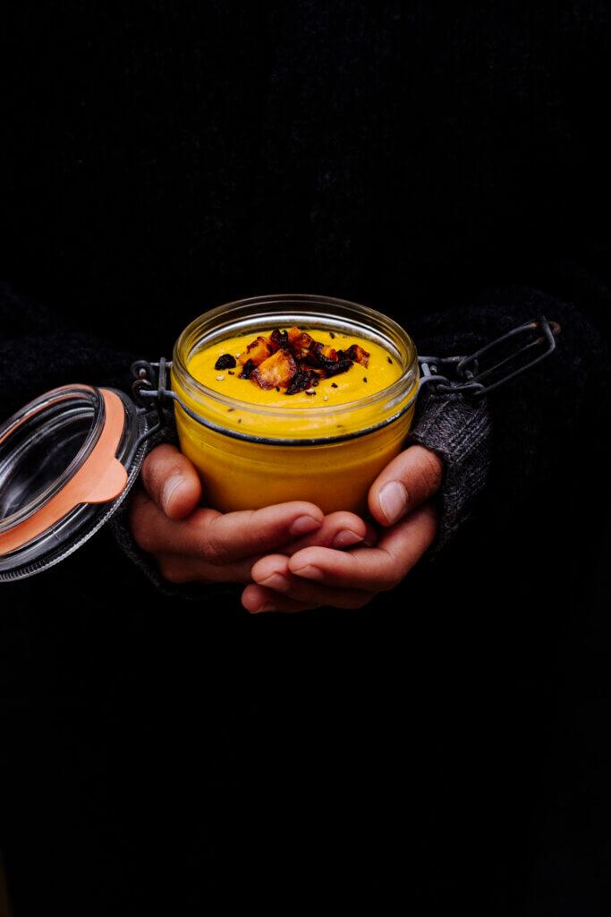 Hand hält Glas mit Karotensuppe