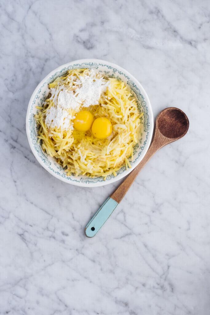 Schüssel mit geriebenen Kartoffeln und Ei