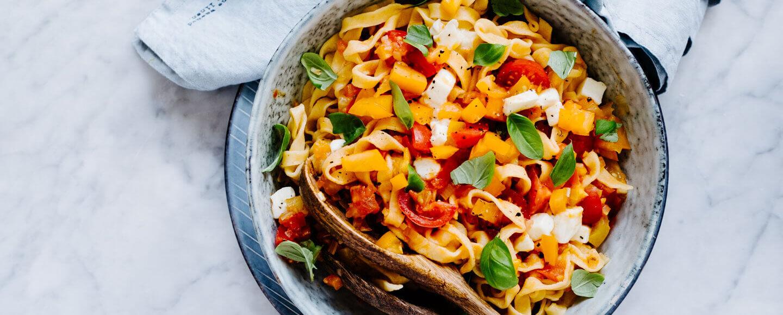 Pasta mit Tomaten-Sugo in Schüssel auf Marmorplatte