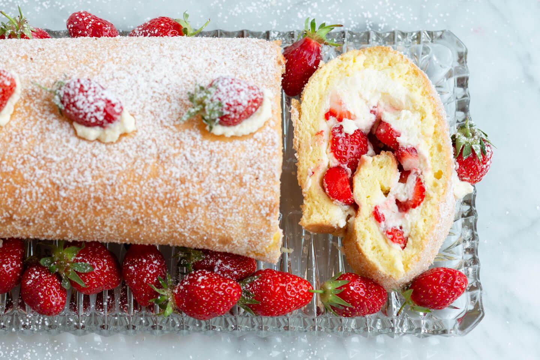 Biskuitrolle mit Sahne und Erdbeeren auf Kuchenplatte
