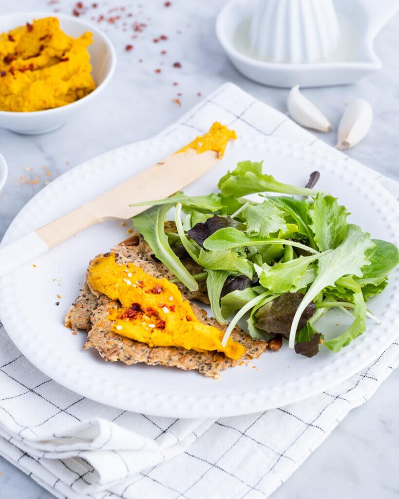 Kürbisaufstrich mit Salat und Cracker auf weißem Teller